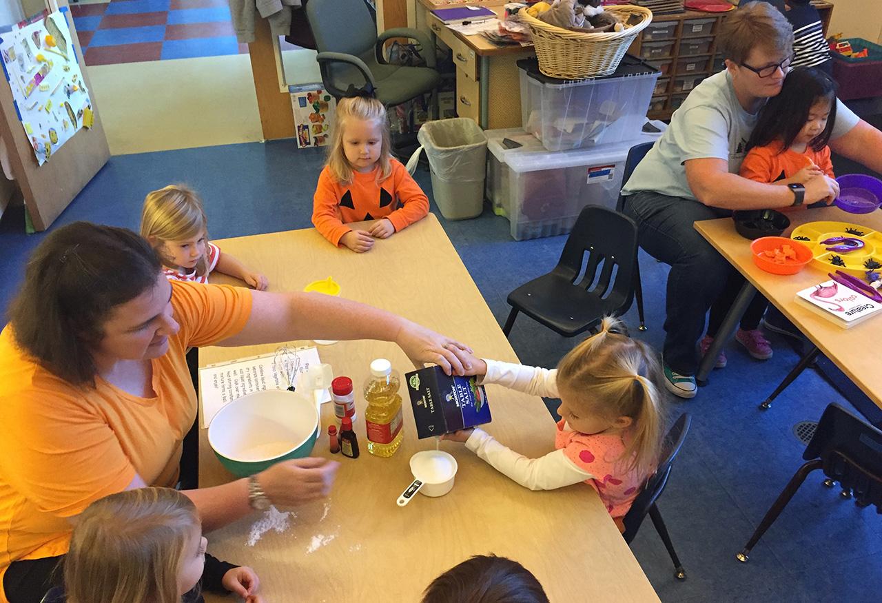 Preschoolers mixing dough